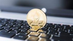 Guld- Ethereum mynt på en bärbar dator Ethereum crypto valuta på ett bärbar datorsvarttangentbord Digital pengar och faktiskt Royaltyfria Bilder