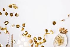 Guld- färgdekor och konfettier på den vita bakgrunden arkivbild