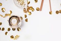 Guld- färgdekor och konfettier på den vita bakgrunden royaltyfri bild
