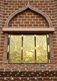 Guld- fönster av väggen Arkivfoto