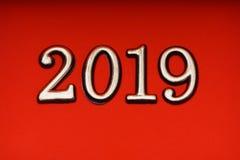 Guld 2019 för mall för hälsningkortdesign på röd bokstäver Arkivfoto