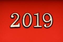 Guld 2019 för mall för hälsningkortdesign på röd bokstäver Arkivbild