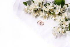 Guld- förlovningsring med jasminblommor och band på en vit bakgrund Fotografering för Bildbyråer