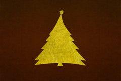 Guld- fiber för julträd på mörk textur för brunt papper Royaltyfria Foton