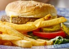 guld- franska småfiskar för cheeseburger Arkivbilder
