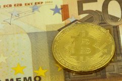 Guld- fysisk Bitcoin cryptocurrency mot en sedel för euro 50 Royaltyfri Foto