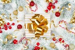Guld- gåva eller närvarande ask, snöig granträd och julgarneringar på den vita träbästa sikten för tabell Lekmanna- lägenhet royaltyfri fotografi
