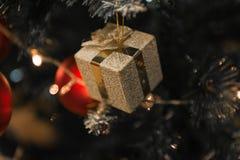 Guld- gåva för jul på härligt ett omgivet Chrismas träd fotografering för bildbyråer