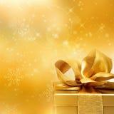 Guld- gåva med en ögla och en julbakgrund arkivfoton