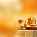 Guld- gåva med en ögla och en julbakgrund royaltyfri foto