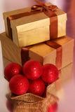 Guld- gåva och röda julbollar Fotografering för Bildbyråer
