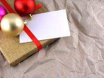 Guld- gåvaask med det röda bandet, julbollar och det tomma kortet Fotografering för Bildbyråer