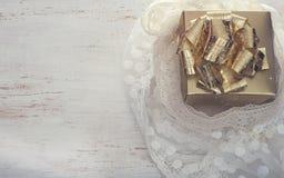 Guld- gåvaask på den vita tabellen Royaltyfria Bilder