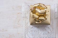 Guld- gåvaask på den vita tabellen Royaltyfri Bild