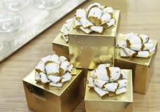 Guld- gåvaaskar med vita pilbågar på en trätabell royaltyfria foton