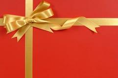 Guld- gåvabandpilbåge, röd bakgrund för gåvasjal, kopieringsutrymme Royaltyfria Bilder