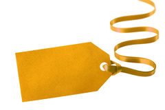 Guld- gåvaetikett som binds med det lockiga bandet som isoleras på vit Arkivfoto