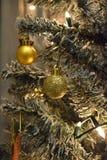 Guld- garneringar i en vit julgran Arkivfoto
