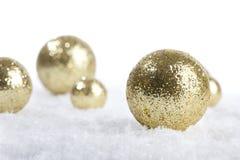 Guld- garneringbollar för jul på snö Arkivfoton