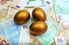 Guld- ägg som sitter på pengar Arkivbilder