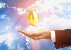 Guld- ägg över den manliga handen Fotografering för Bildbyråer