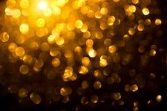 Guld- glödande bakgrund för jul Semestra den abstrakta defocused bakgrunden Suddig guld- bokeh för glitter på svart royaltyfri fotografi