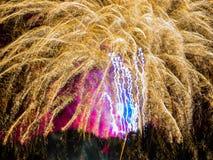 Guld- gnistrande med rosa färger och blått spektakulära fyrverkerier Fotografering för Bildbyråer