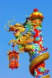 Guld- gragonstaty på röd pelare i templet Arkivfoton
