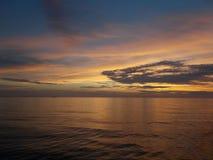 Guld- gryning för guld- soluppgång över en slät yttersida för hav royaltyfri bild