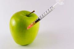 Guld- gula Apple och hypodermatisk injektionsspruta Arkivfoto