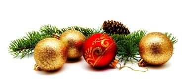 Guld- guling för julgarnering och röda bollar med grankottar arkivfoton