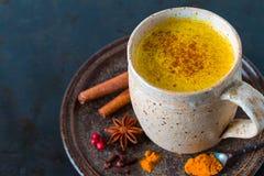 Guld- gurkmeja mjölkar latte med kanelbruna pinnar royaltyfria foton