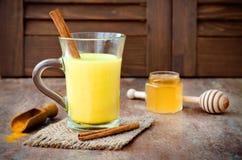 Guld- gurkmeja mjölkar latte med kanelbruna pinnar och honung Fet gasbrännare för Detoxlever, immun ökning, anti-upphetsande drin Arkivfoto