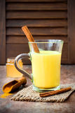 Guld- gurkmeja mjölkar latte med kanelbruna pinnar och honung Fet gasbrännare för Detoxlever, immun ökning, anti-upphetsande drin Fotografering för Bildbyråer