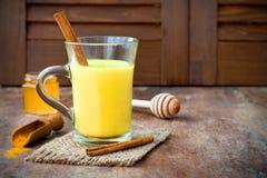 Guld- gurkmeja mjölkar latte med kanelbruna pinnar och honung Fet gasbrännare för Detoxlever, immun ökning, anti-upphetsande drin Arkivbilder