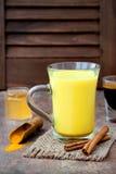 Guld- gurkmeja mjölkar latte med kanelbruna pinnar och honung Fet gasbrännare för Detoxlever, immun ökning, anti-upphetsande drin Royaltyfri Foto