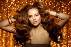 Guld- härlig modekvinna, modell med skinande sunt långt v Arkivfoto