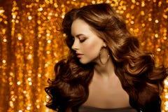 Guld- härlig modekvinna, modell med skinande sunt långt v Arkivbild