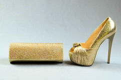 Guld hög-heeled sko- och kopplingpåsen på en grå bakgrund Royaltyfri Fotografi