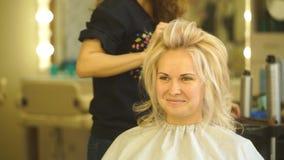 Guld- - haired blond flicka som gör volymen som krullar vid frisören i skönhetsalongen lager videofilmer