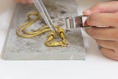 Guld- halsbandhandhantverk på stenen Arkivfoto