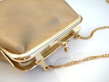 guld- handväska för bakgrund över white Arkivfoton