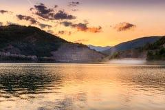Guld- himmel och dramatiska fluffiga moln över den reflekterande silkeslena sjön och dammmolnet som flyger över vattnet Royaltyfri Bild