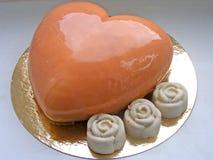 Guld- hjärta för kakamousse med bärmousse i spegelglasyren med rosor arkivfoton