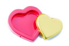 Guld- hjärtaform för choklad på den röda asken royaltyfri fotografi
