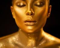 Guld- hudkvinnaframsida Closeup för modekonststående Modellera flickan med makeup för guld- glamour för ferie skinande yrkesmässi royaltyfri bild