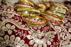 Guld- indiska armband för kvinna` s ligger på en sari Arkivbilder