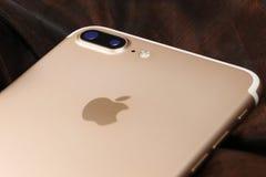 Guld- iPhone 7 Plus på abstrakt bakgrund Arkivfoton