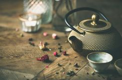 Guld- järntekanna, koppar, torkad ros, stearinljus över träbakgrund Royaltyfri Foto