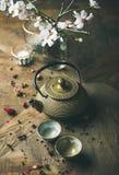 Guld- järntekanna, koppar, torkad ros, stearinljus och mandelblommor Arkivbilder